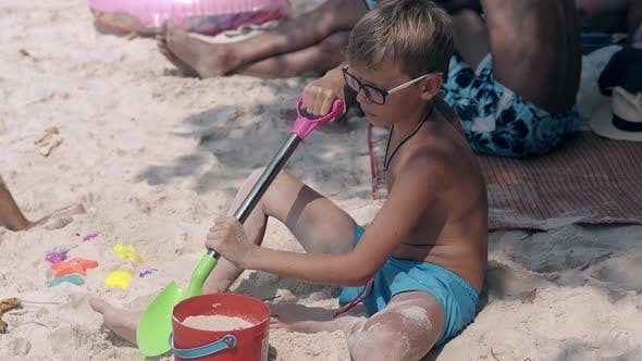 Thumbnail for Blond Boy in Glasses Plays with Kids Spade and Sows Sand