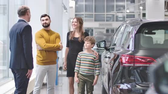Thumbnail for Four Caucasian People Standing Next To New Automobile in Car Dealership