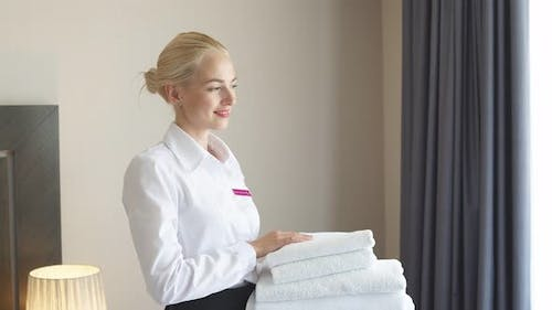 Attractive Chambermaid with Towels in Hands