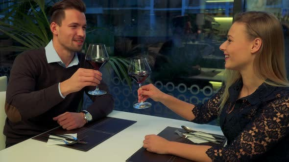 Thumbnail for A Man and a Woman Sit at a Restaurant, He Proposes a Toast, They Drink Wine, Hold Hands and Talk