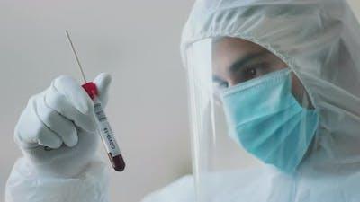 Man in hazmat suit looking at test-tube