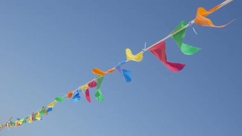 Slow motion colorful pennant banner crowd control rope against blue sky 1080p HD footage - Many flag