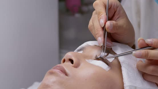 Thumbnail for Gluing artificial eyelashes with tweezers on woman eye, Eyelash extension
