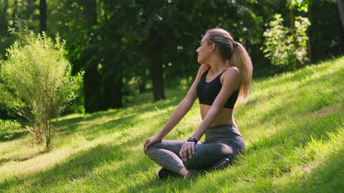 Young Girl Meditating in Public Park, Feeling Unity with Nature