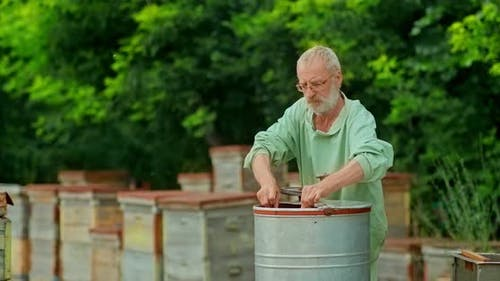 Beekeeper Inserts the Honeycomb Frame Into the Honey Extractor. Beekeeper Turns the Handle of the