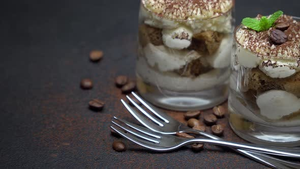 Cover Image for Two Portions Classic Tiramisu Dessert in a Glass on Dark Concrete Background