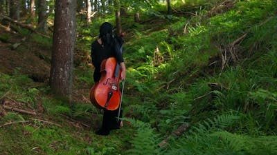 Young woman with cello in woods