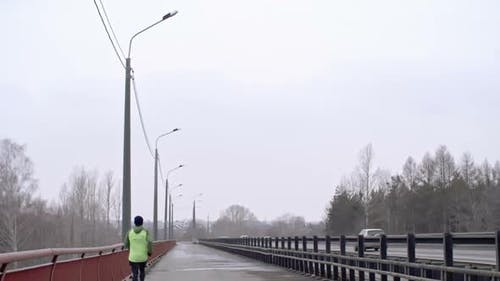 Man Jogging on Bridge in Dull Weather