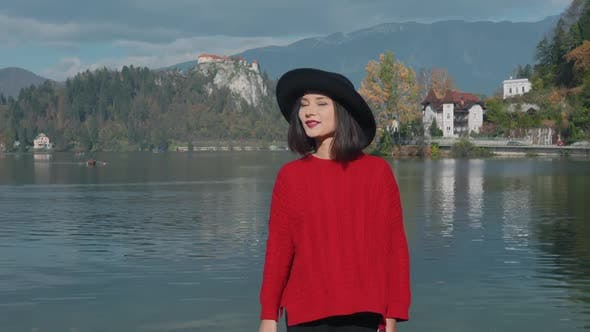Thumbnail for Smiling Cheerful Asian Woman Wearing Big Black Hat Goes Posing for the Camera Blowing a Kiss