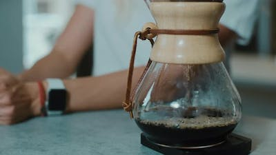 Barista making the aroma of  Filter coffee for female costumer.