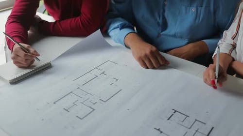 Young People Studying New Blueprints at Office