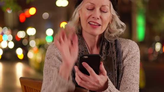 Thumbnail for Joyful elder woman texting on phone laughing in urban setting with bokeh lights