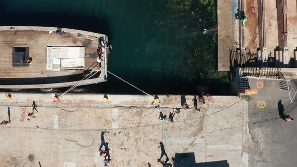 Thumbnail for Boat Tied to a Port and People Swimming and Walking by the Path