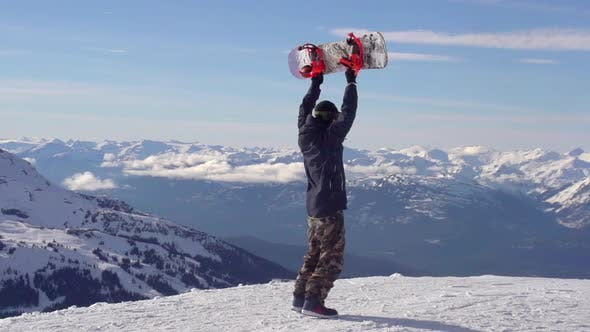A young man snowboarder standing with his snowboard on a snow covered mountain.
