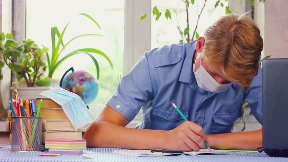 Teenager in blauer medizinischer Maske des kaukasischen Zugehörigkeit sitzt an seinem Schreibtisch an seinem Schreibtisch