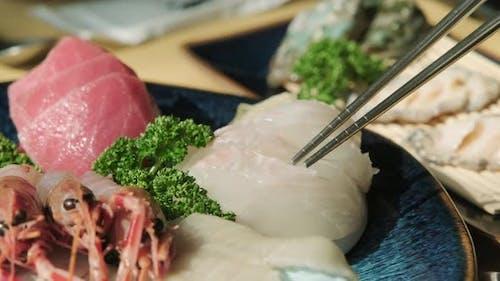 Fresh Japanese sashimi lifted with chopsticks