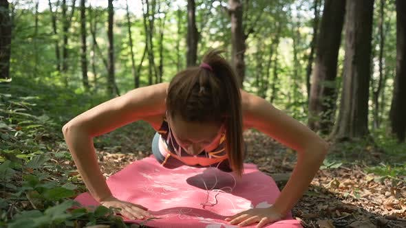 Thumbnail for Active Girl, Concentrated in Workout Doing Push Ups on Pink Pilates Mat in the Forest