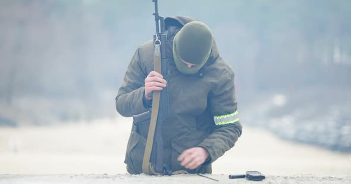 Portrait of Serious Focused Recruit Disassembling Military Weapon Outdoors