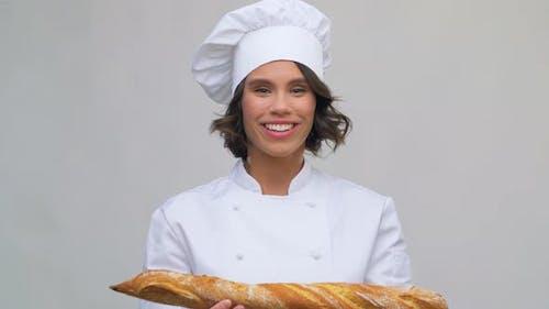 Heureuse cuisinière avec pain français ou baguette