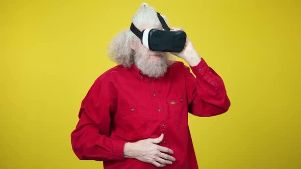 Thumbnail for Portrait of Senior Greyhaired Man Wearing Virtual Reality Simulator Looking Around and Laughing Out