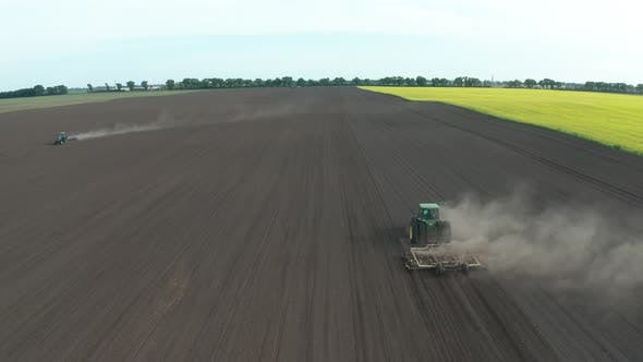 Thumbnail for Aerial View of Tractors Harrowing Field for Sowing