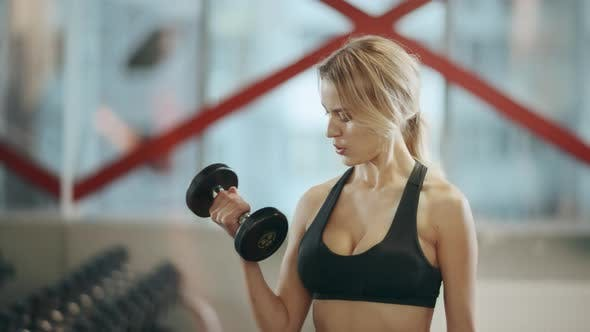 Thumbnail for Blonde Female Trainer Doing Dumbbells Exercises in Fitness Gym