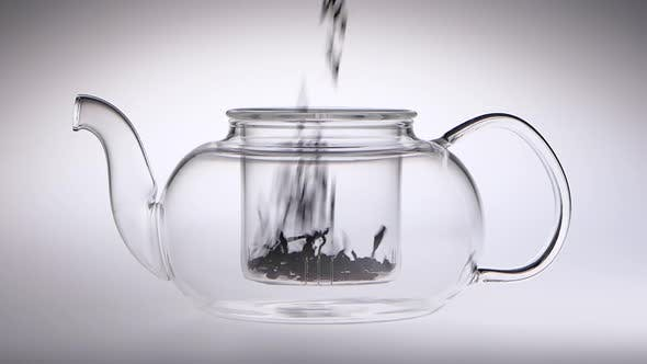 Thumbnail for Tea Leaves Are Falling in Glass Transparent Teapot. Slow Motion