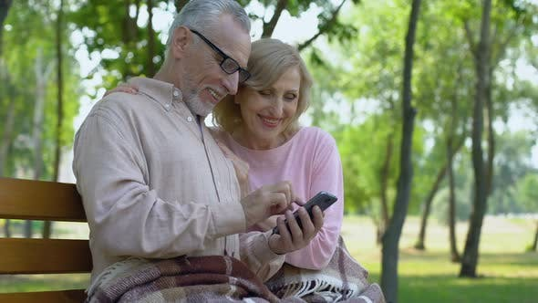 Thumbnail for Grandfather and Grandmother Admiring Children Photos in Smartphone Application