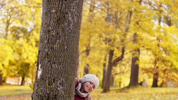 Thumbnail for Happy Family Hiding Behind Tree at Autumn Park