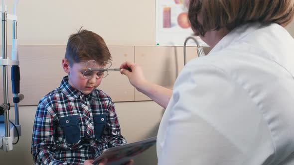 Thumbnail for Ophthalmologist Treatment - Checking the Eyes of a Little Boy - a Boy Reading Letters From the
