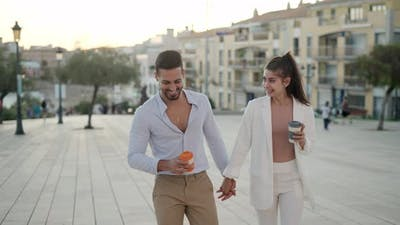 Trendy Hispanic Couple Drinking Takeaway Coffee While Strolling on Street
