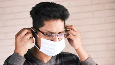Young Asian Man Putting Surgical Face Mask Indoor