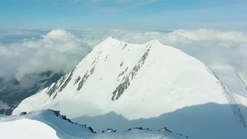 Snowy Top of Mountain in European Alps in Sunny Day. Aerial View