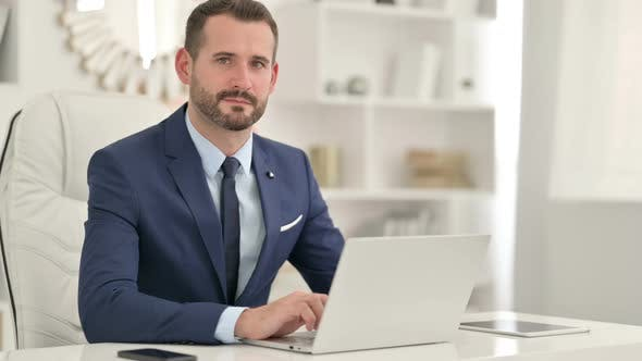 Thumbnail for Serious Businessman with Laptop Looking at the Camera