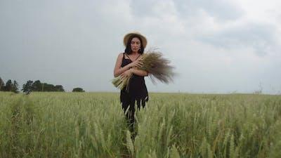 Girl In A Straw Hat Walks On A Wheat Field