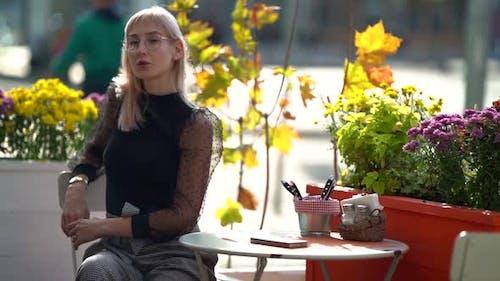 Porträt eines attraktiven blonden Mädchens mit Brille, das auf einer Stadtstraße in einem Café an einem Tisch sitzt