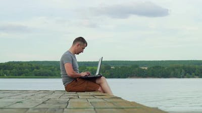 Man on the pier working on a laptop. Work on vacation