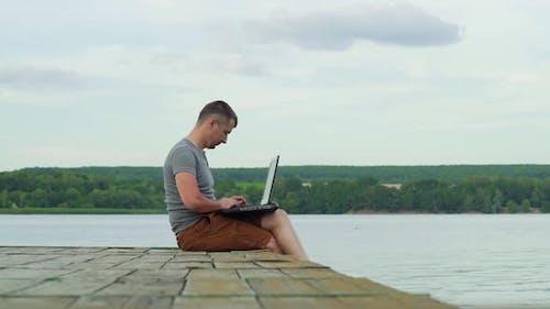 Mann am Pier arbeitet an einem Laptop. Arbeite im Urlaub