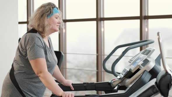 Overweight Woman Exercising on a Treadmill at a Gym