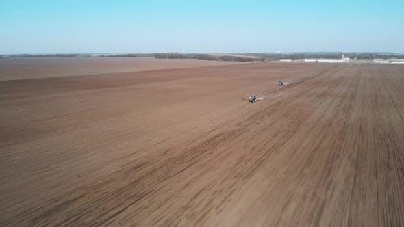 Thumbnail for Two tractors fertilize a field