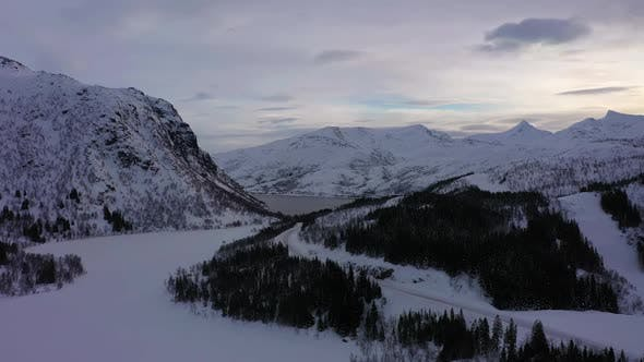 Frozen Lake and Mountains in Winter Morning. Troms, Norway. Aerial View