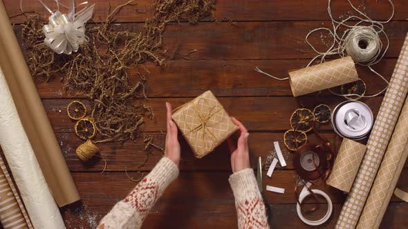 Thumbnail for Female Hands Turning Christmas Present on Wooden Table