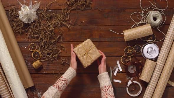 Thumbnail for Weibliche Hände drehen Weihnachtsgeschenk auf Holztisch