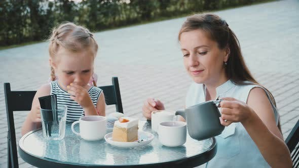 Cover Image for Mother with Daughter Drinks Tea in Cafe