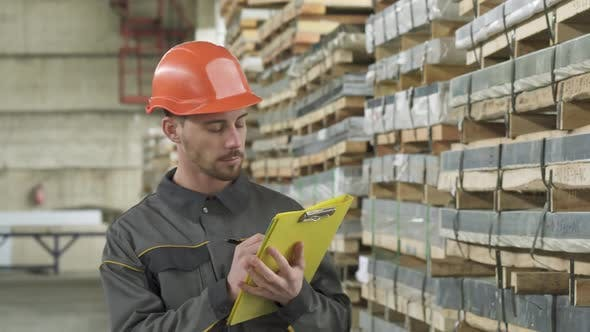 Thumbnail for Handsome Male Warehouse Worker Walking Writing on His Clipboard