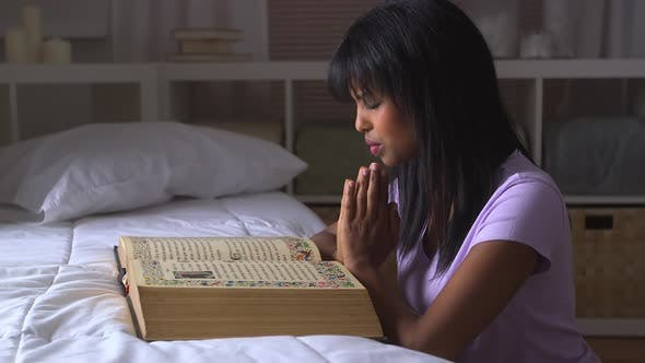 Thumbnail for Black girl praying with Bible on bed
