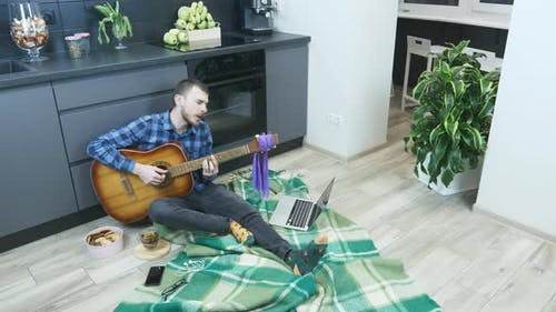 Young musician is singing and playing lyrical ballads on acoustic guitar