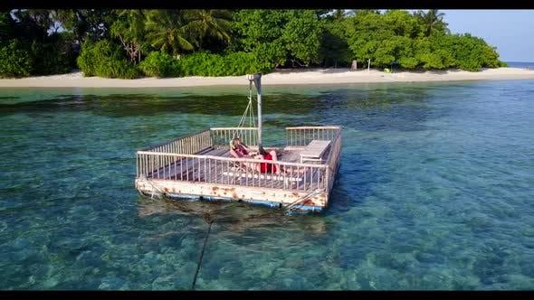 Thumbnail for Teenage lovers sunbathing on idyllic coastline beach wildlife by blue water and white sandy backgrou