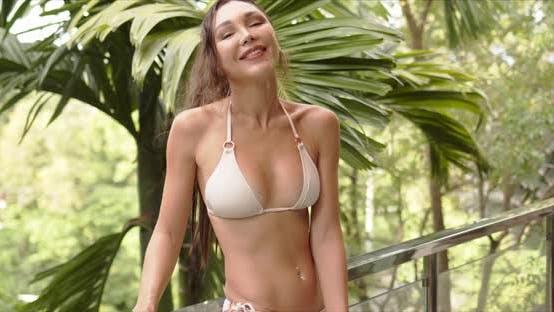 Smiling Woman in Swimwear on Balcony