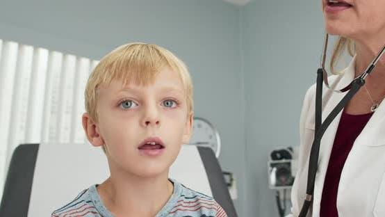 Female pediatrician using stethoscope to listen to breathing of little boy